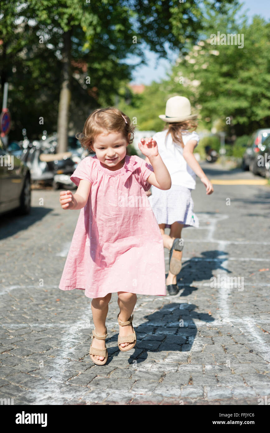 Two girls playing hopscotch on cobblestone - Stock Image