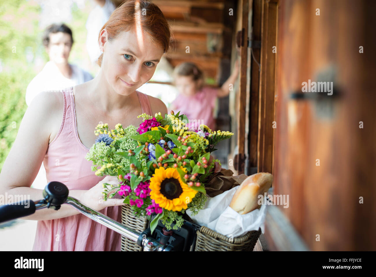Portrait of mid adult woman with flowers - Stock Image
