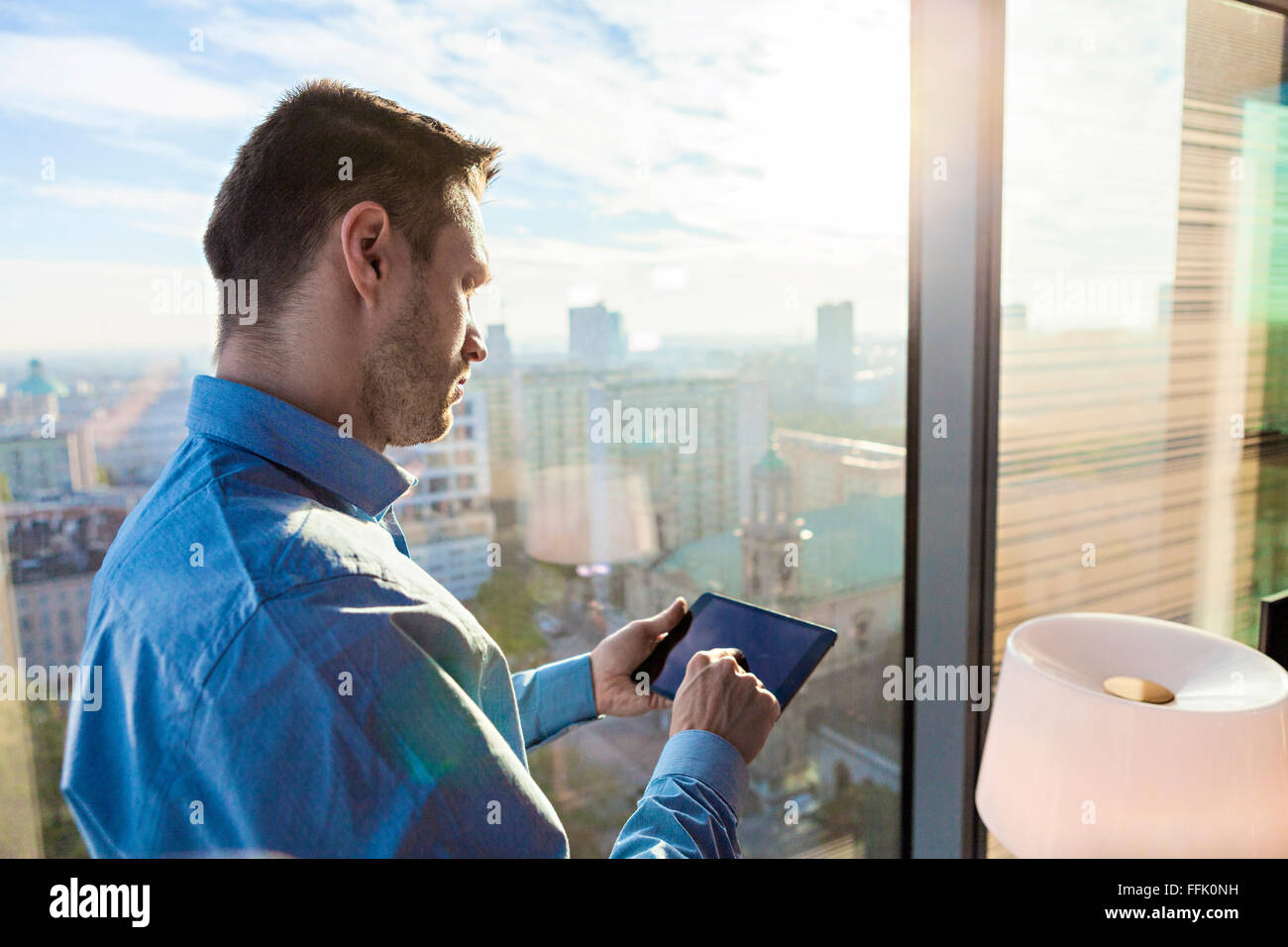 Businessman in apartment using digital tablet - Stock Image