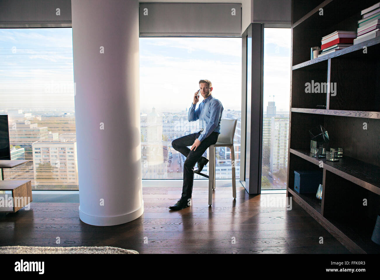 Businessman in apartment on the phone - Stock Image