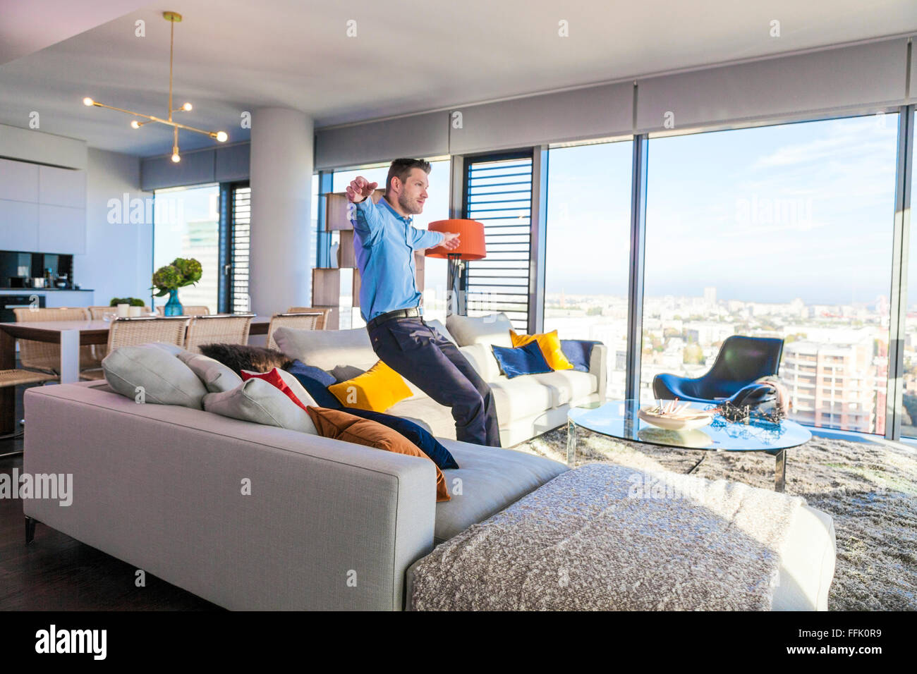 Man in apartment relaxing arms outstretched - Stock Image