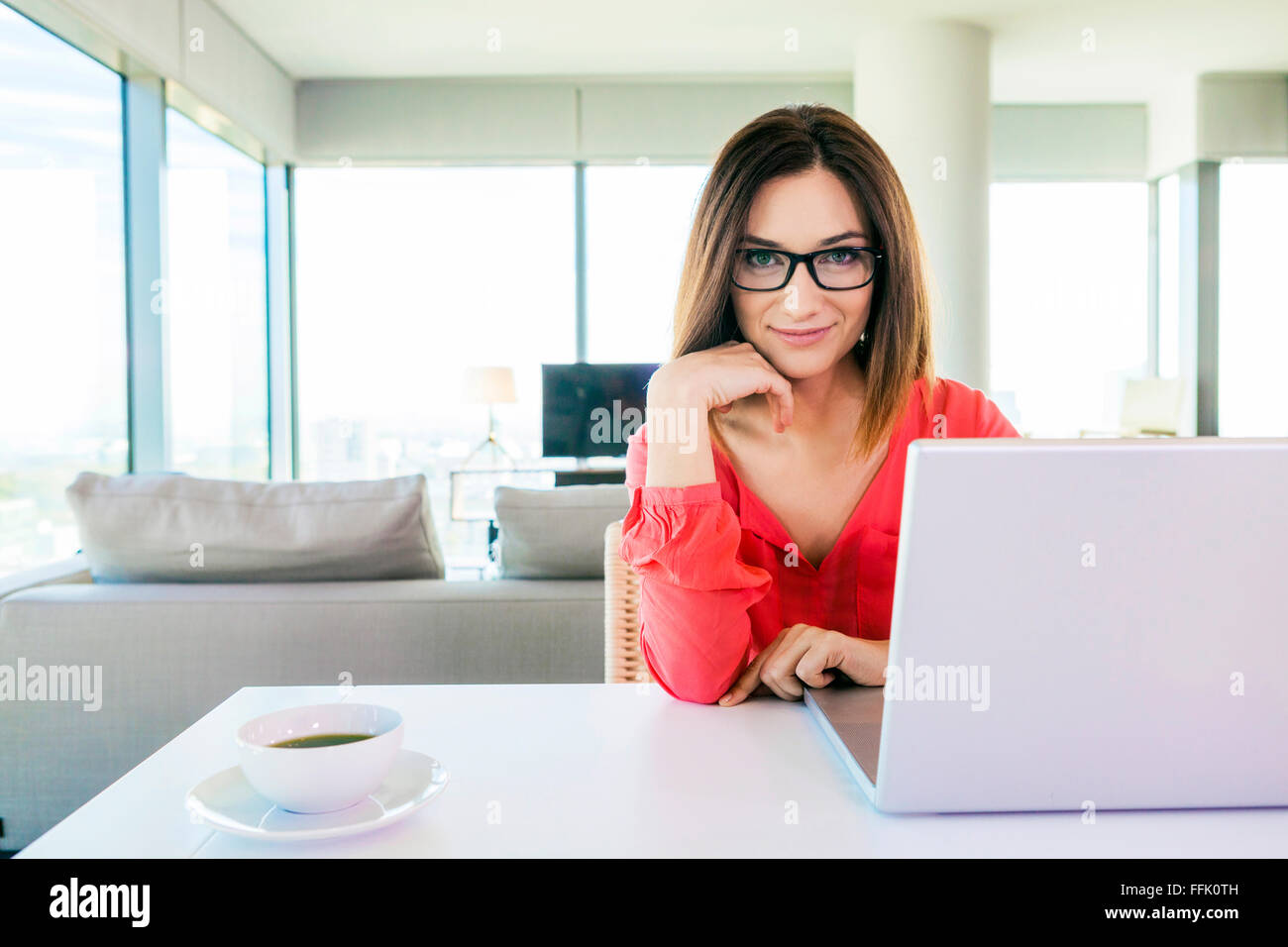 Woman in apartment using laptop computer - Stock Image