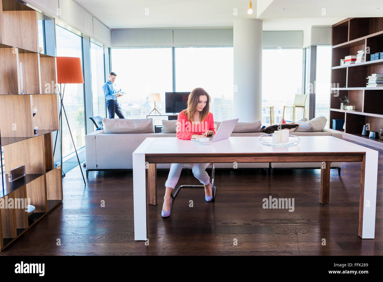 Woman in apartment using laptop with man in background - Stock Image