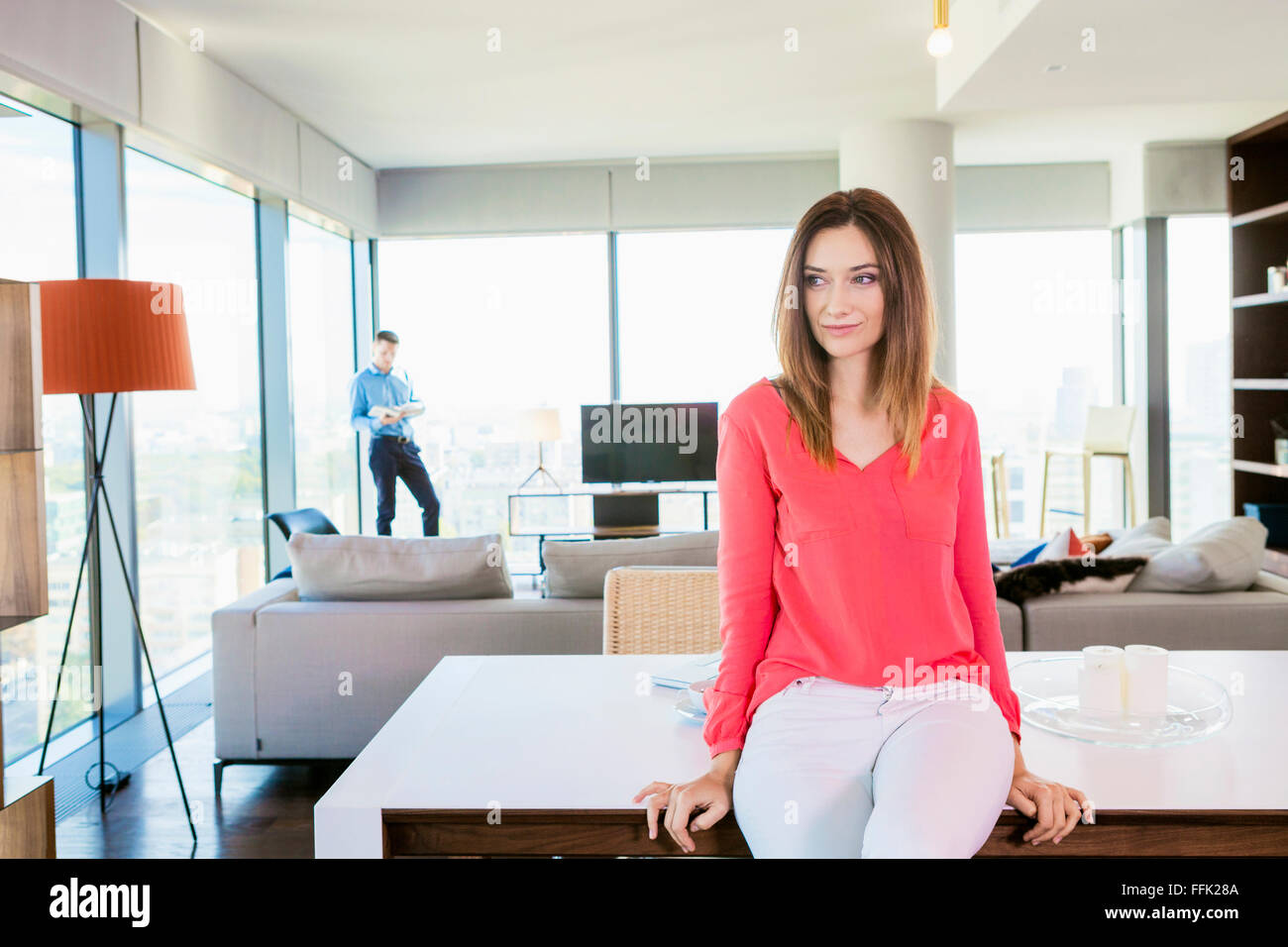 Woman in apartment day dreaming with man in background - Stock Image