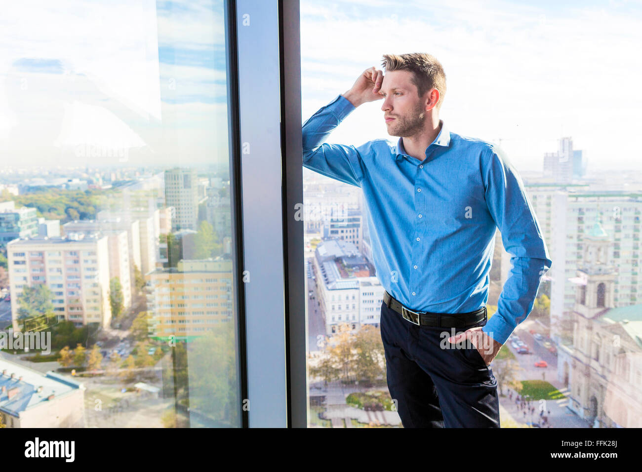 Businessman in apartment looking through window - Stock Image