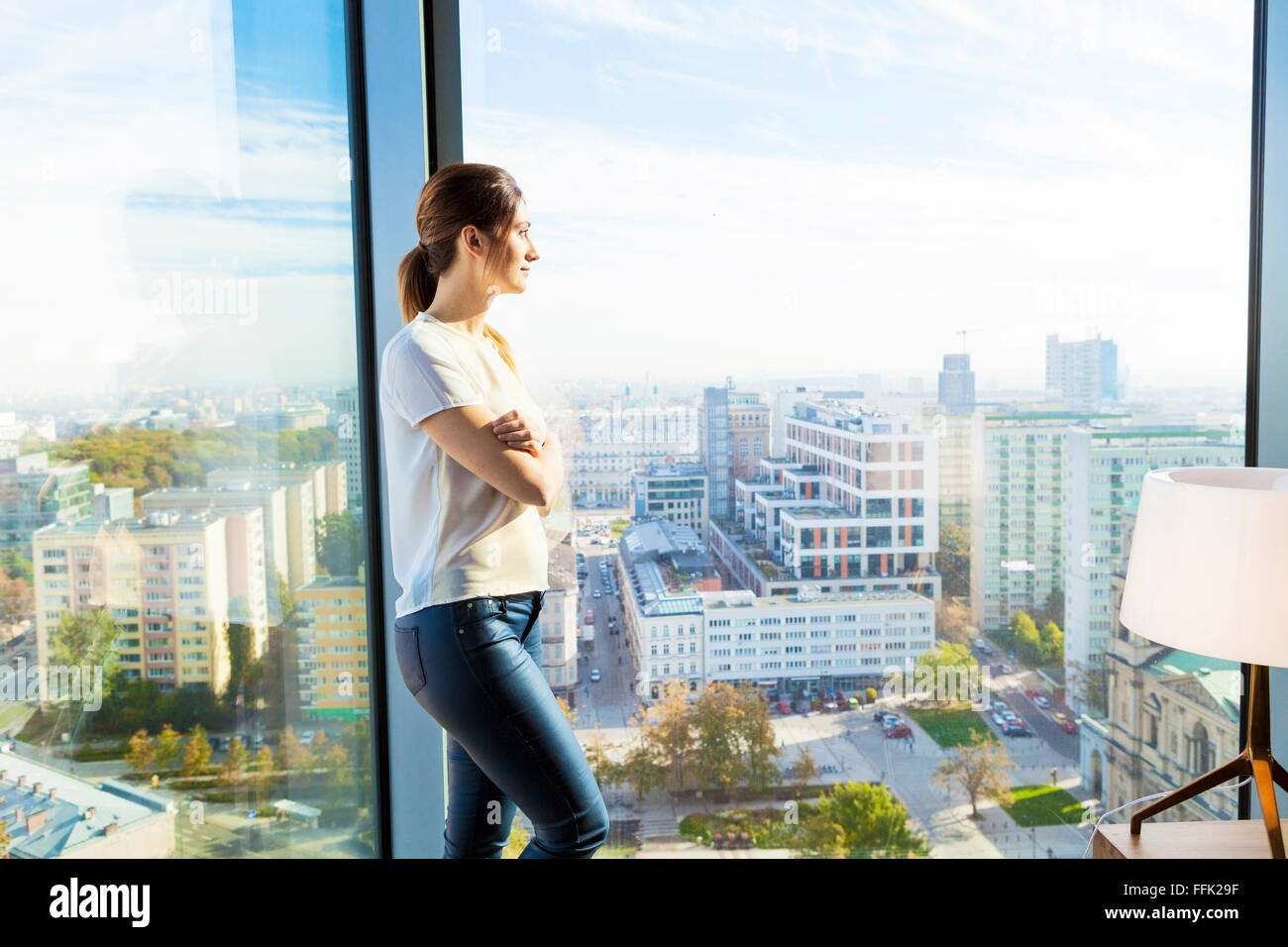Woman in apartment looking through window - Stock Image