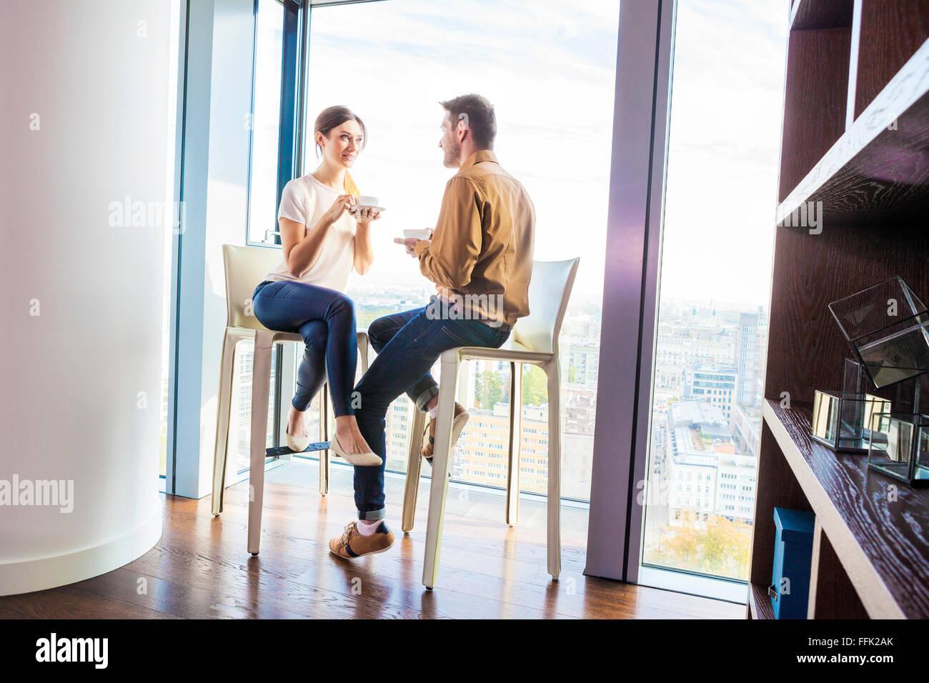Couple in apartment having a coffee break Stock Photo