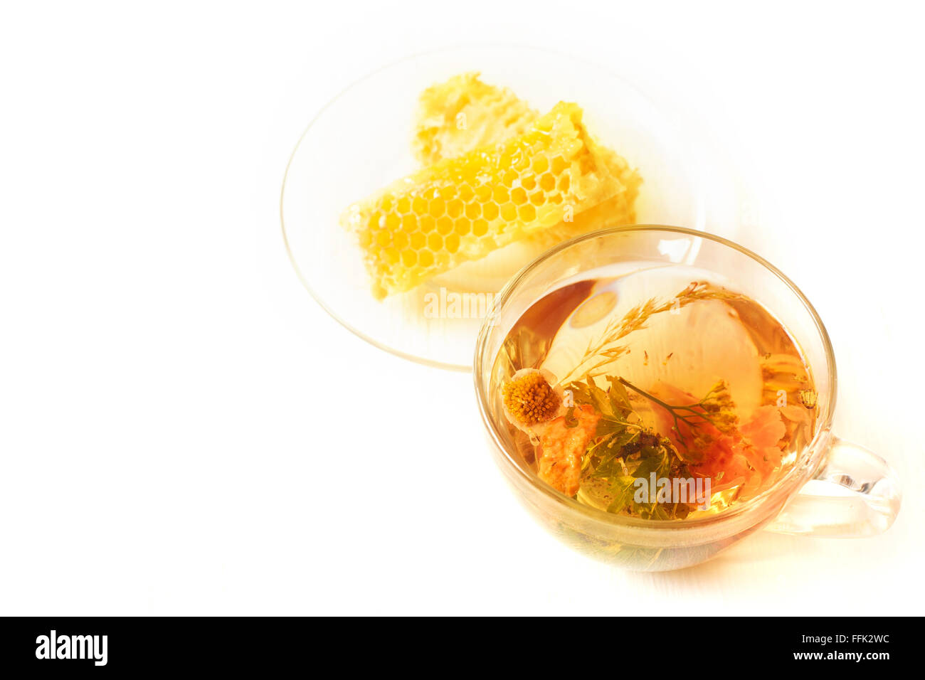 Herbal tea and honeycomb on a white table - Stock Image