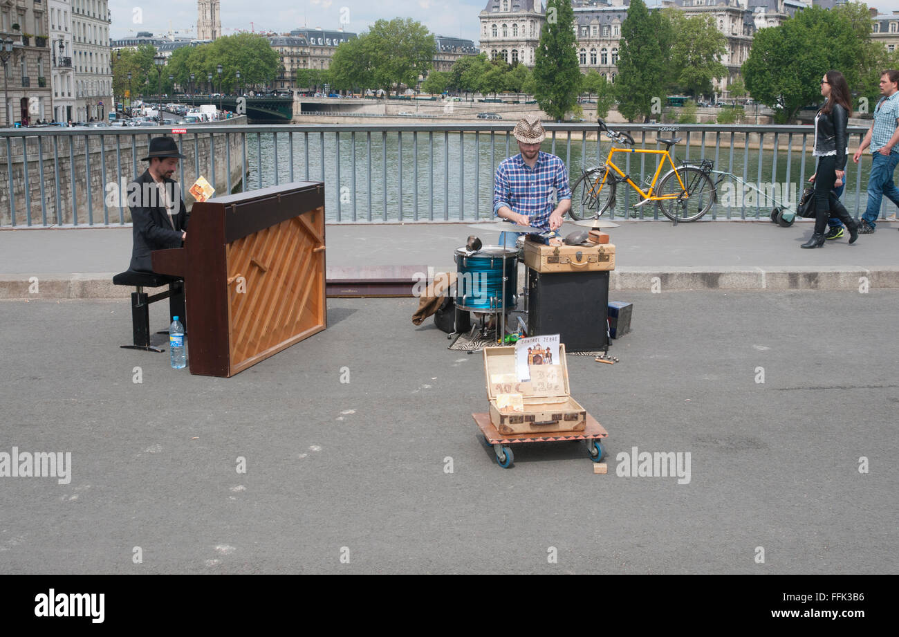 Buskers playing playing music on the bridge Pont Saint-Louis, in Paris, France - Stock Image