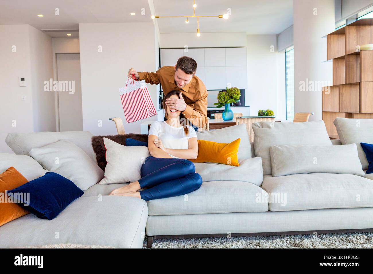 Couple relaxing in modern apartment - Stock Image