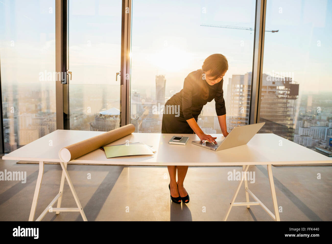 Female architect in office working on laptop - Stock Image