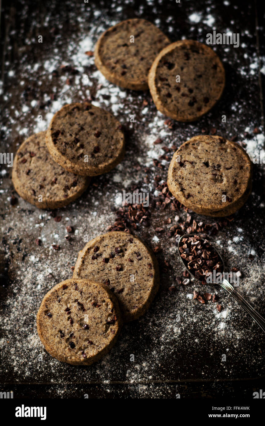 Delicious sable cookies with buckwheat flour, enriched with cocoa nibs. Set up on a dark vintage background - Stock Image