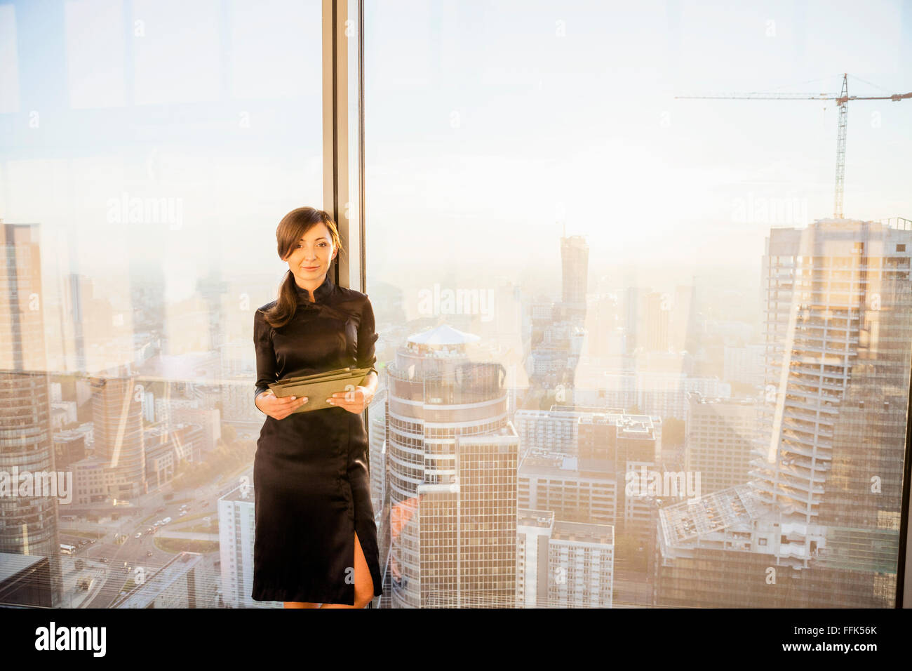 Female architect in office with urban skyline in background - Stock Image
