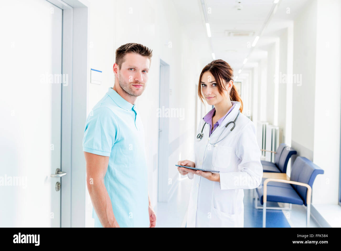 Female doctor and coworker standing in hospital corridor - Stock Image