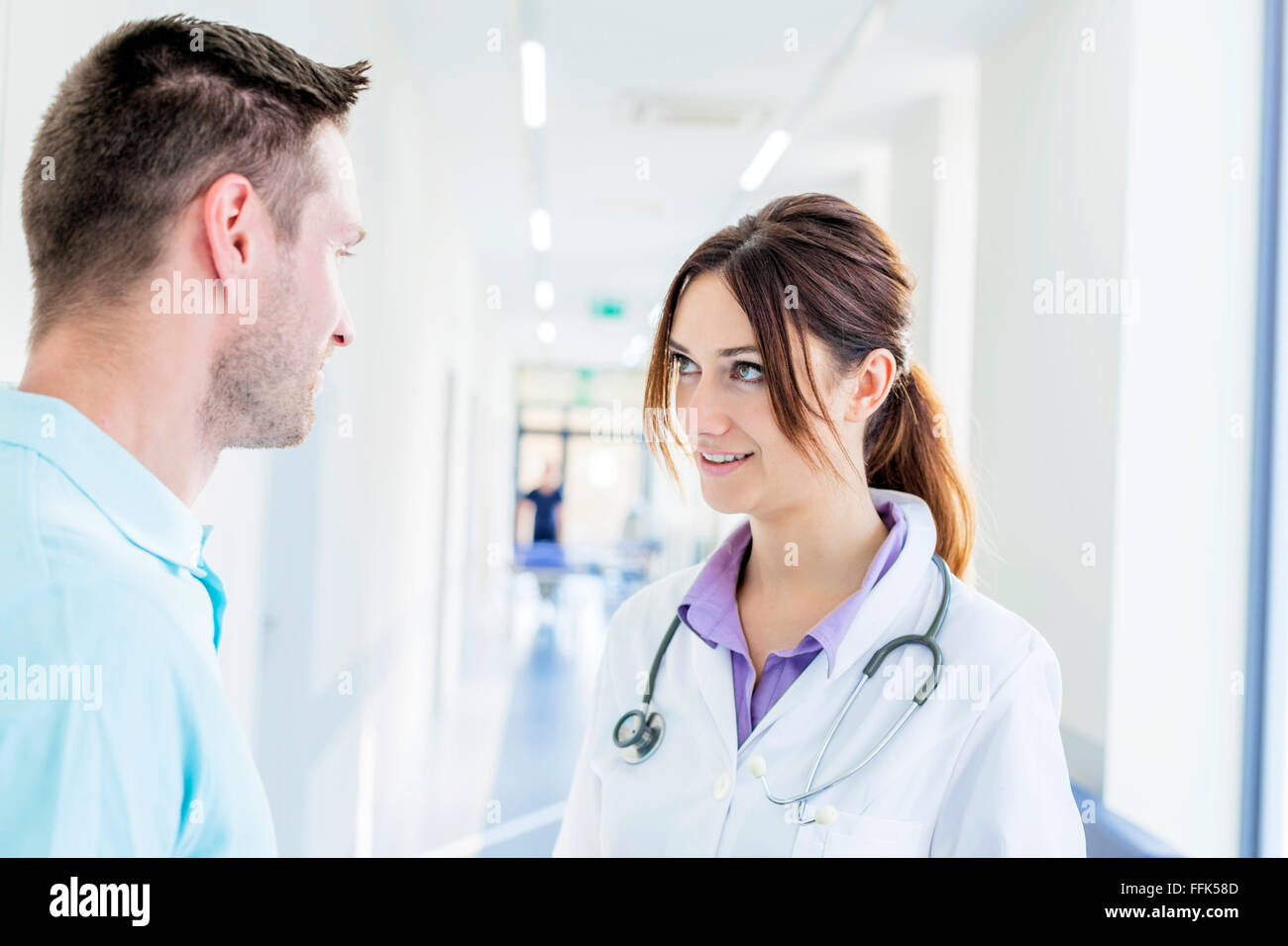 Male and female doctor talking in hospital corridor - Stock Image