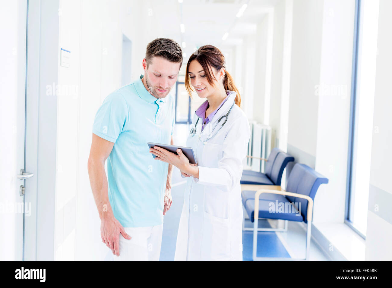 Male and female doctor in hospital corridor using digital tablet - Stock Image