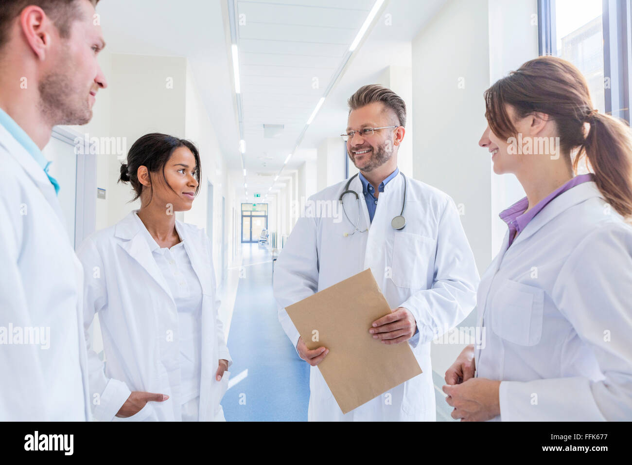 Doctor and coworkers talking in hospital corridor - Stock Image