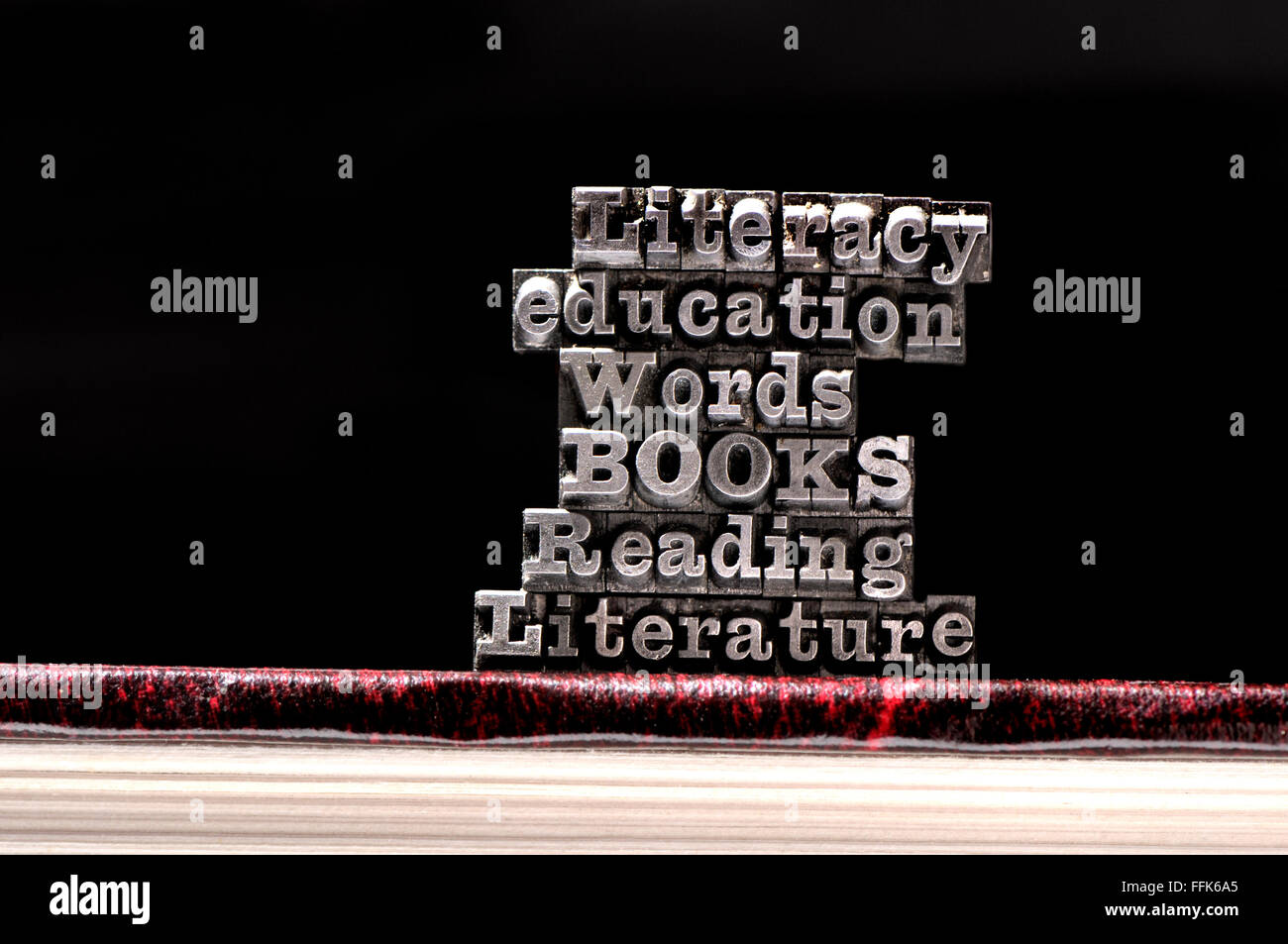 Letterpress characters spelling out educational / literacy words on a book - Stock Image