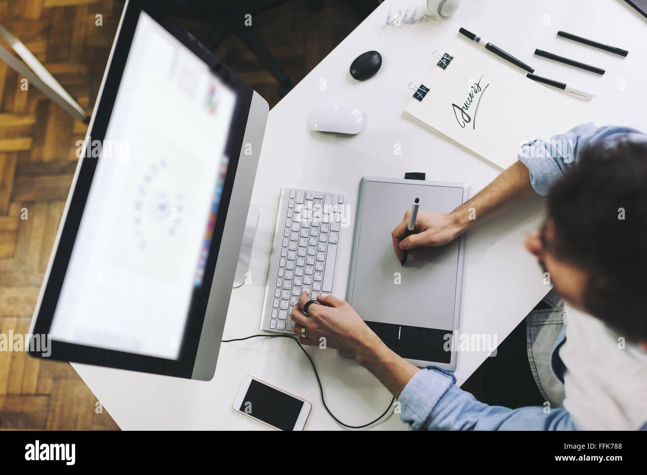 Young graphic designer working in office - Stock Image