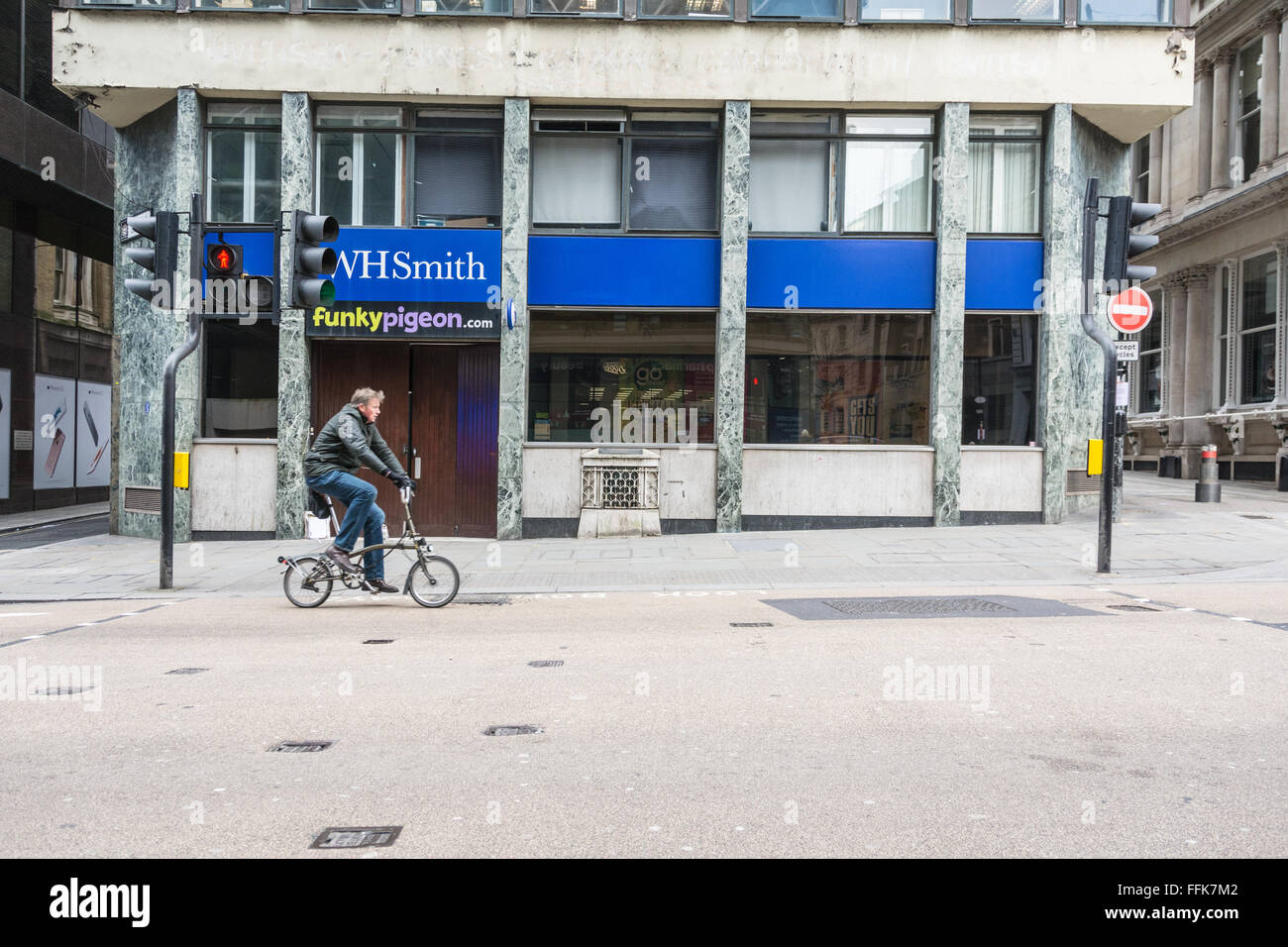 Cyclist passes the ancient London Stone, an historic 900 year old stone hidden behind an iron grille on Cannon Street, - Stock Image
