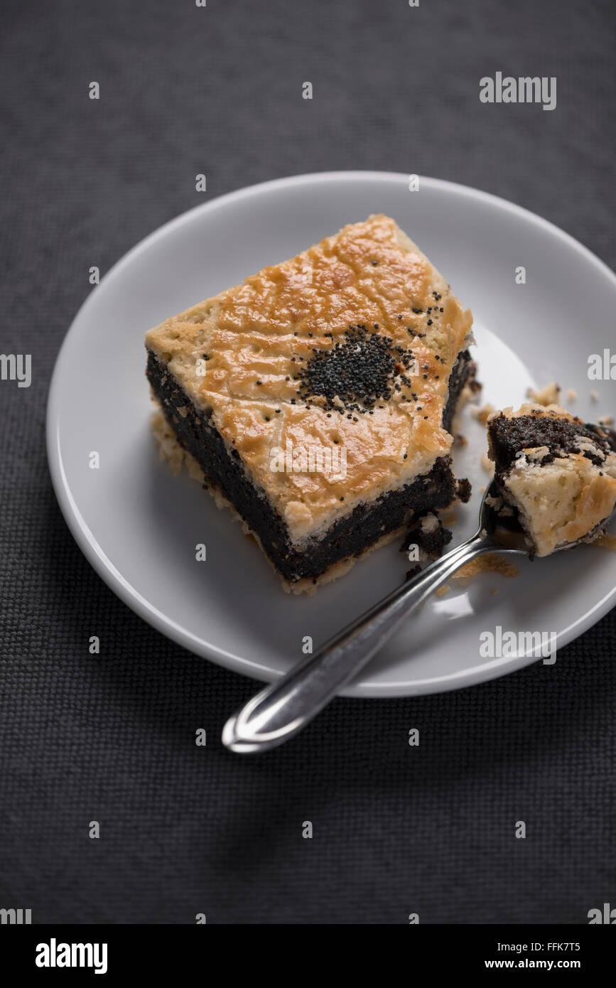 One individual poppy seeds tartlet on a white plate, one bite taken out, with a spoon, on a grey background. - Stock Image