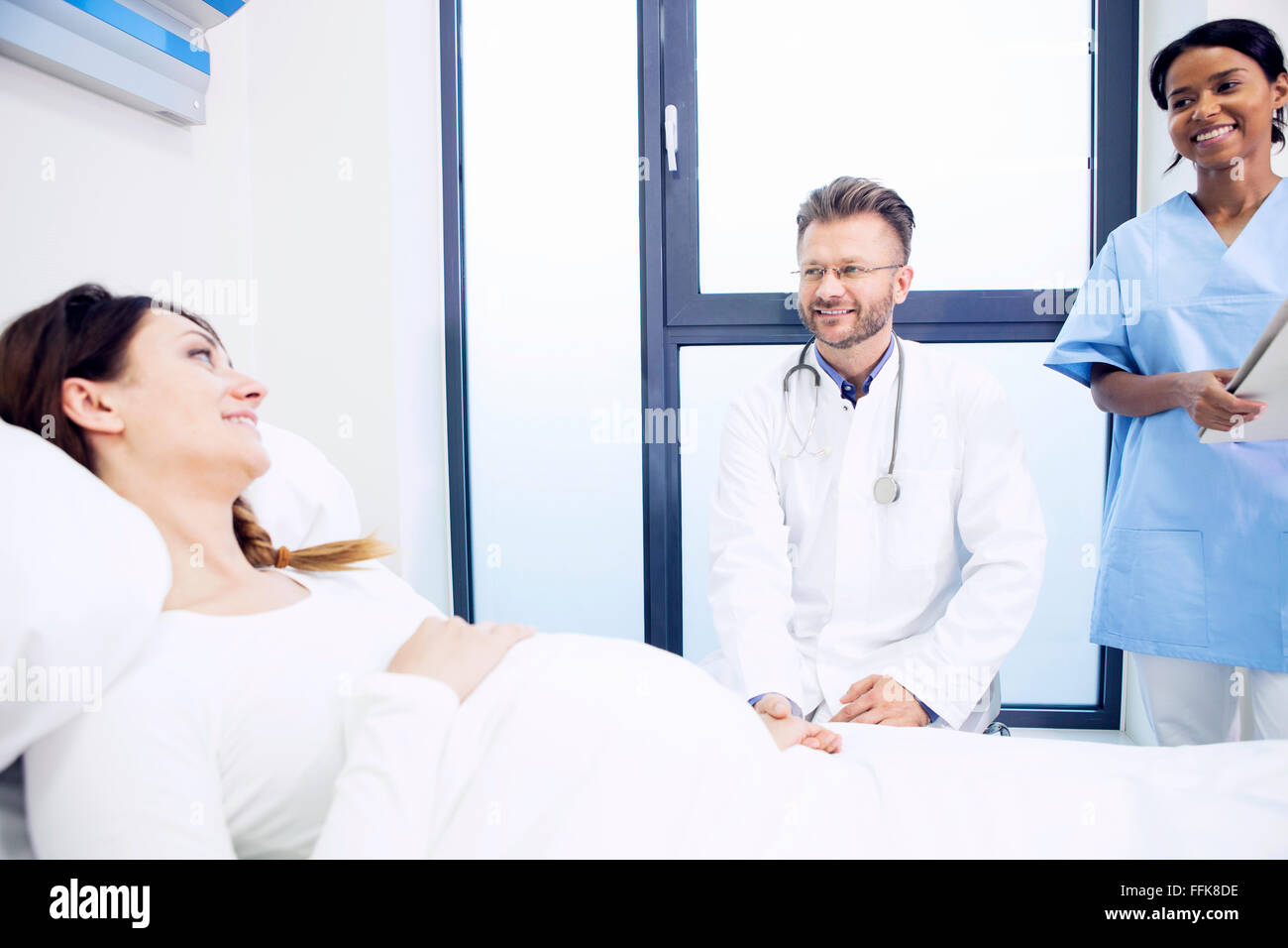 Doctor with patient in sick room of hospital - Stock Image