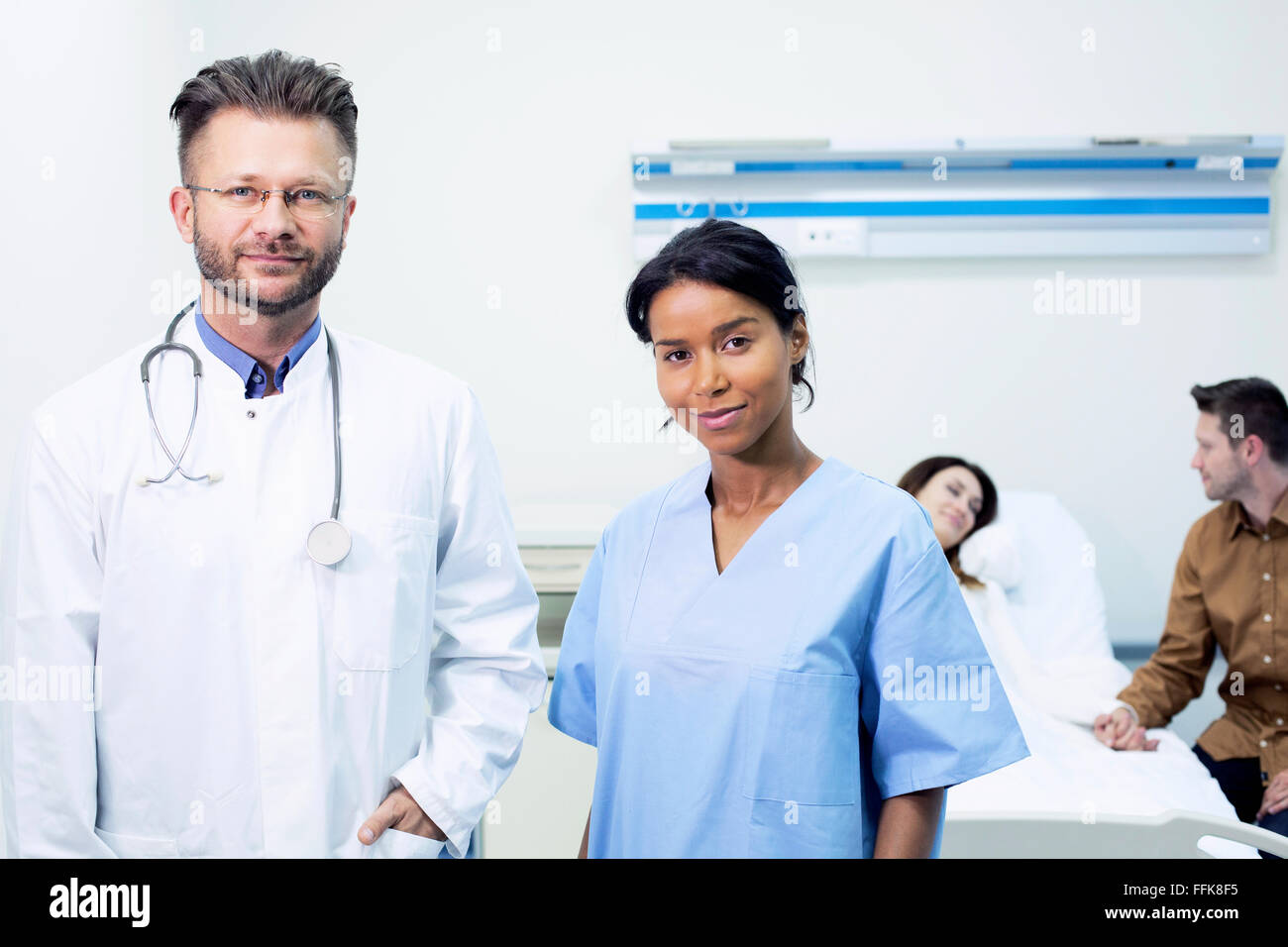 Doctor and healthcare worker in sick room of hospital - Stock Image