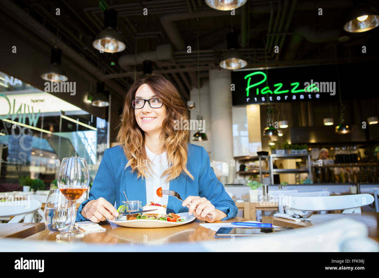 Mid adult woman lunching in restaurant - Stock Image
