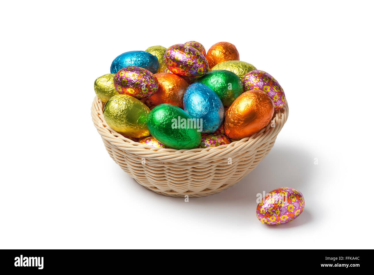 Chocolate Easter eggs in colored foil in a basket - Stock Image