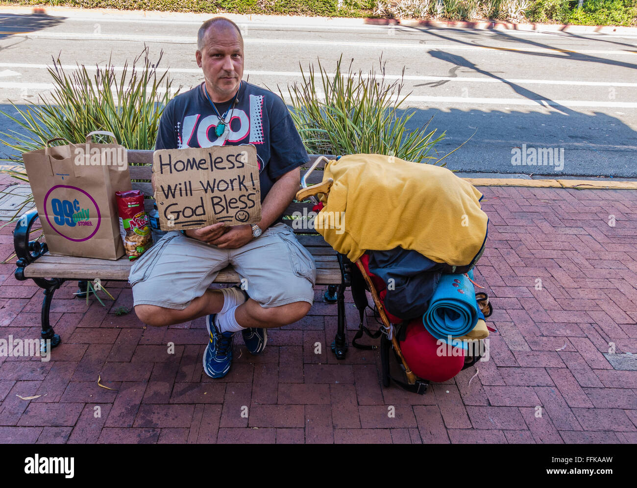 A middle-aged male beggar sits on a public bench on a State Street sidewalk holding a sign that says 'homeless, - Stock Image