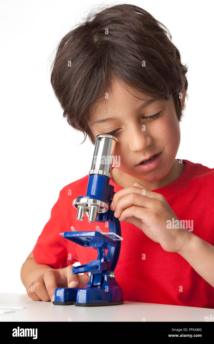 Little boy looking through a microscope on white background - Stock Image