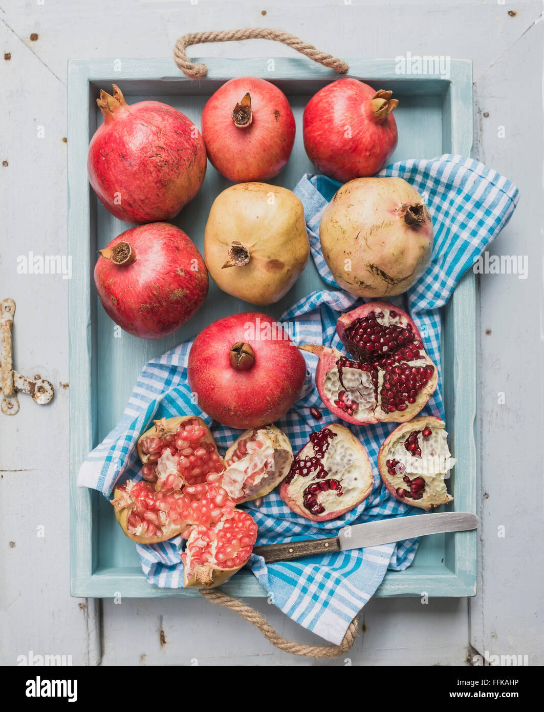 Red and white pomegranates and knife on kitchen towel in blue tray over light painted wooden backdrop, top view Stock Photo