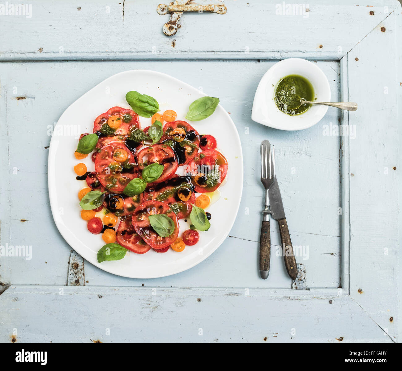 Ripe village heirloom tomato salad with olive oil and basil over light blue wooden background, top view - Stock Image