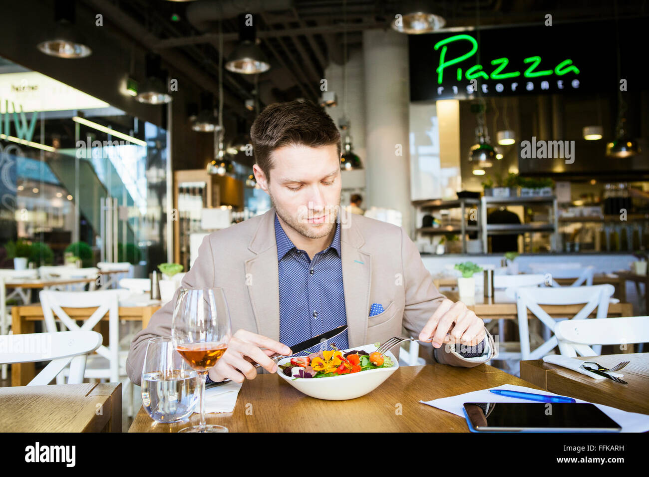 Mid adult man lunching in restaurant - Stock Image