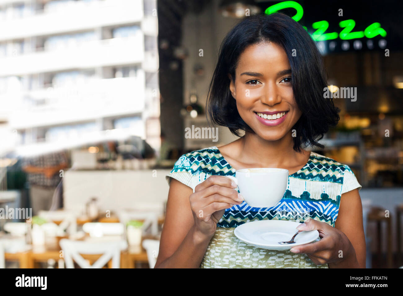 Mixed race woman takes a coffee break - Stock Image