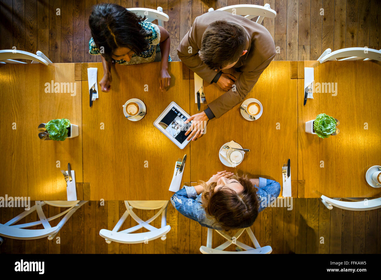 Friends using digital tablet in restaurant - Stock Image