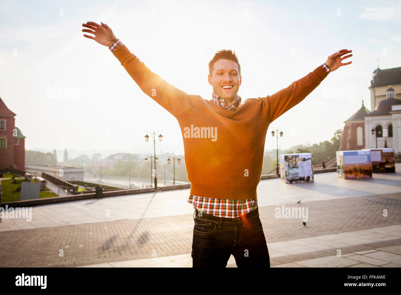 Mid adult man on a city break standing with arms raised - Stock Image