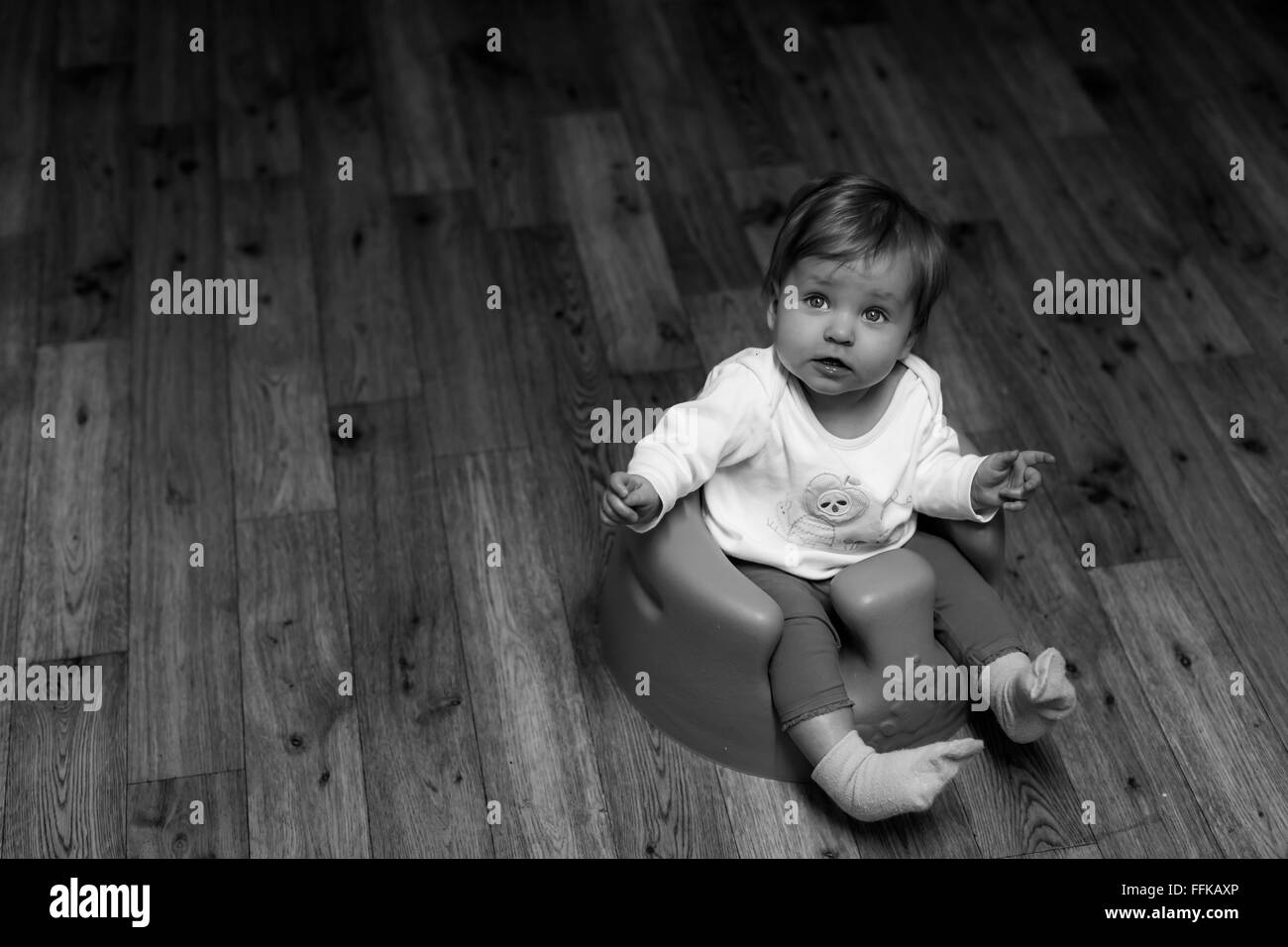 black and white photograph of a beautiful lonely baby sitting in a baby seat on a wooden kitchen floor - Stock Image