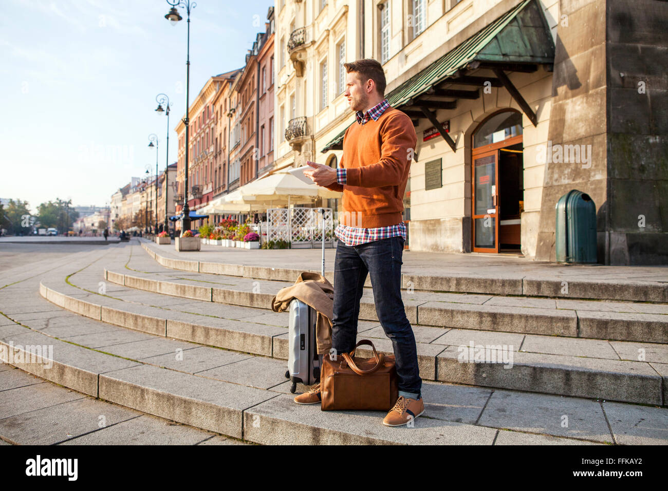 Man on a city break using digital tablet - Stock Image