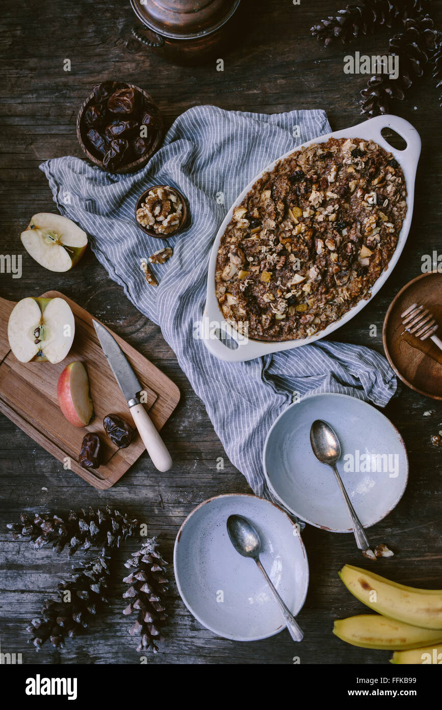Baked oatmeal with apples, dates, bananas, and walnut is just out of the oven, about to be served and displayed - Stock Image