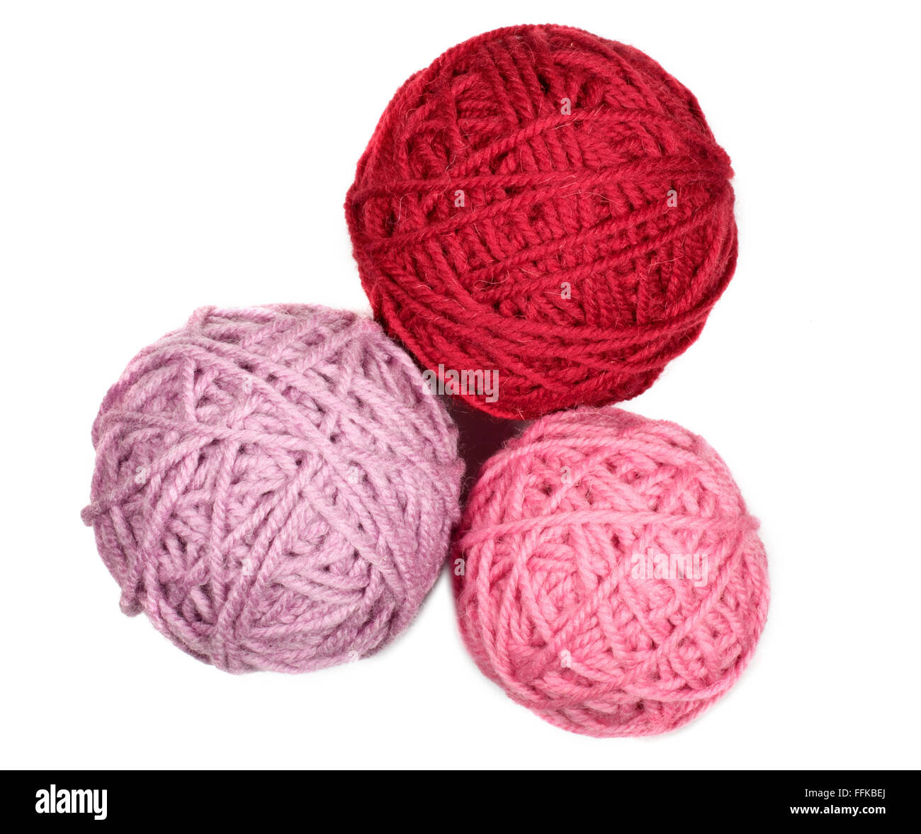 Isolated three skeins in pink over white background macro - Stock Image