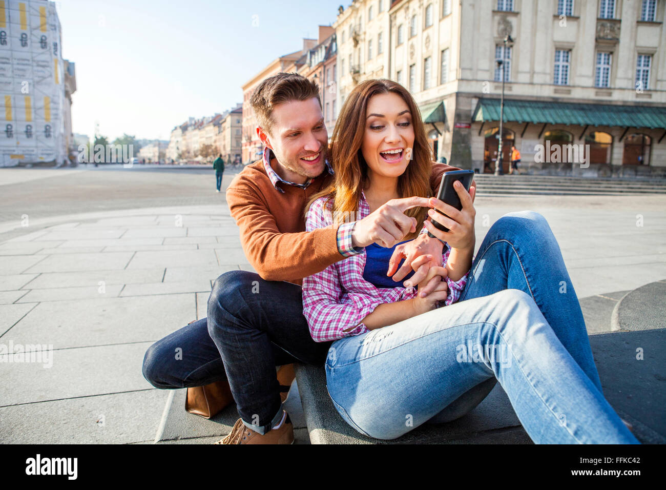 Mid adult couple on a city break using smart phone - Stock Image