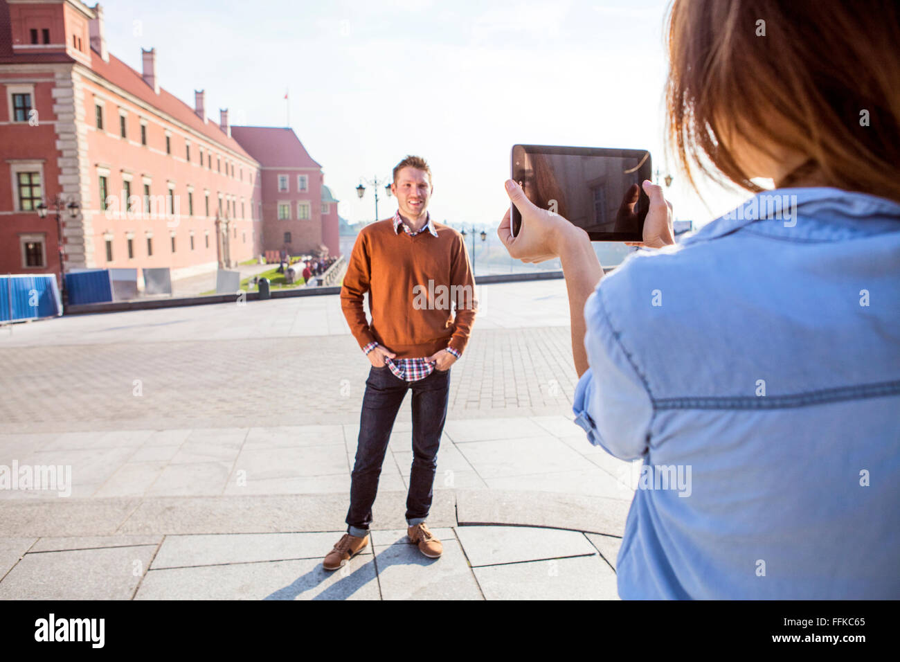 Mid adult woman taking a picture of boyfriend - Stock Image