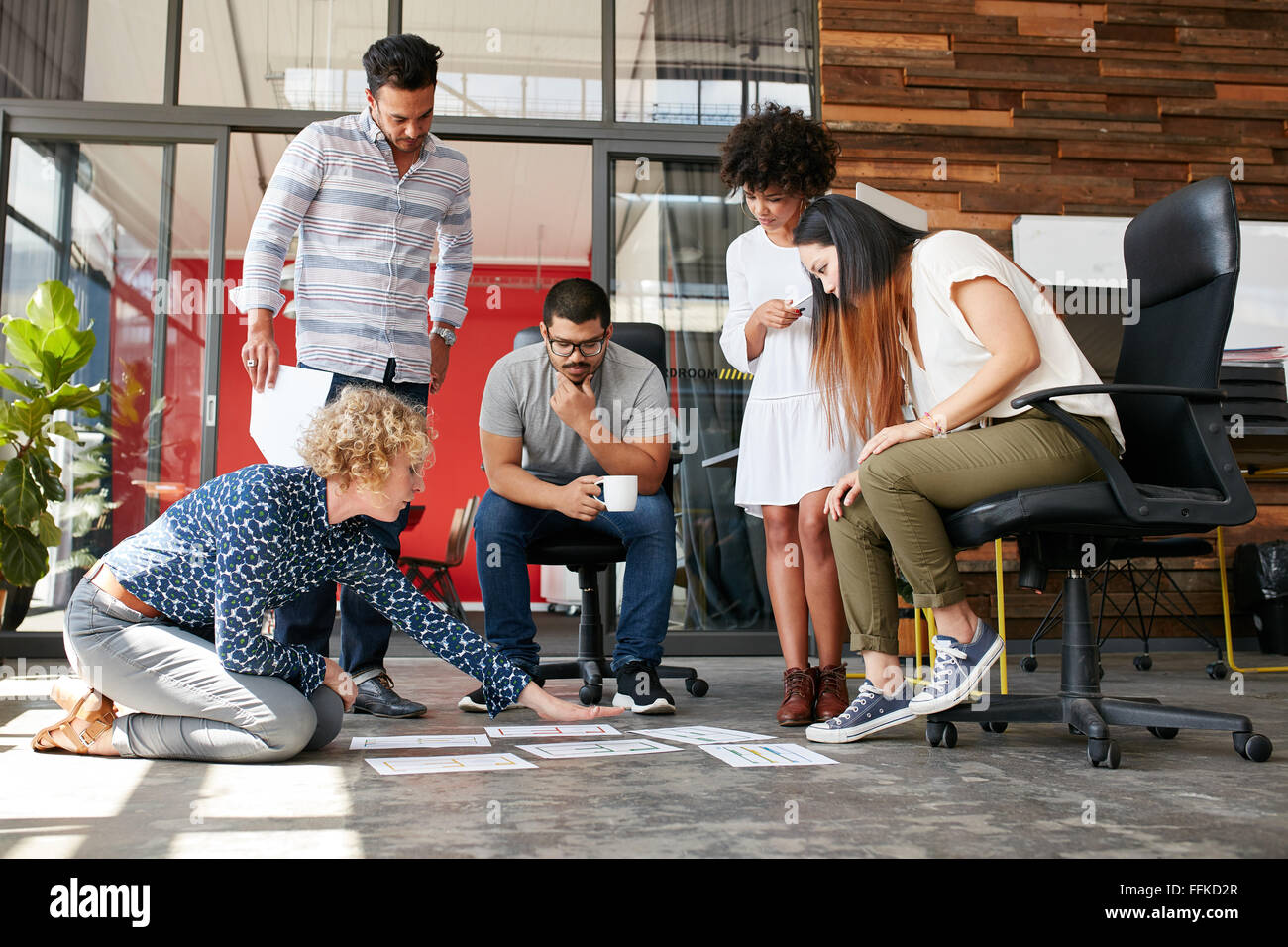 Creative people looking at project plan laid out on floor. Mixed race business associates discussing new project Stock Photo
