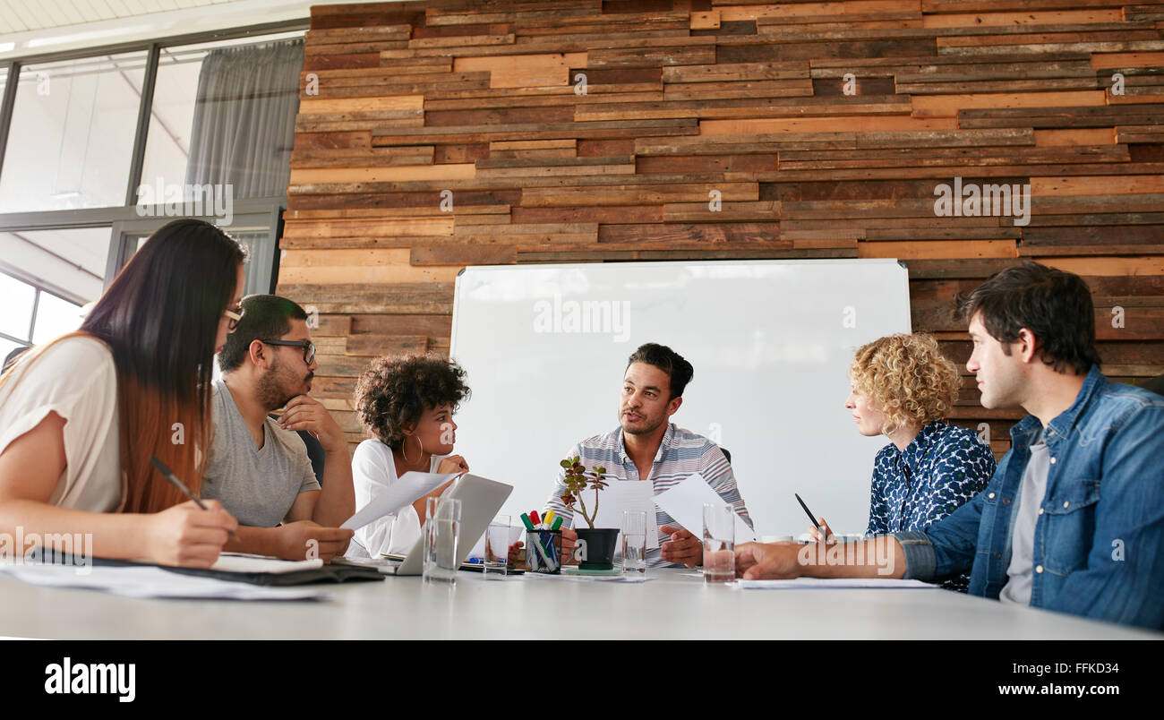 Group of business people having meeting in a board room in an office. Creative team sitting at the table discussing - Stock Image