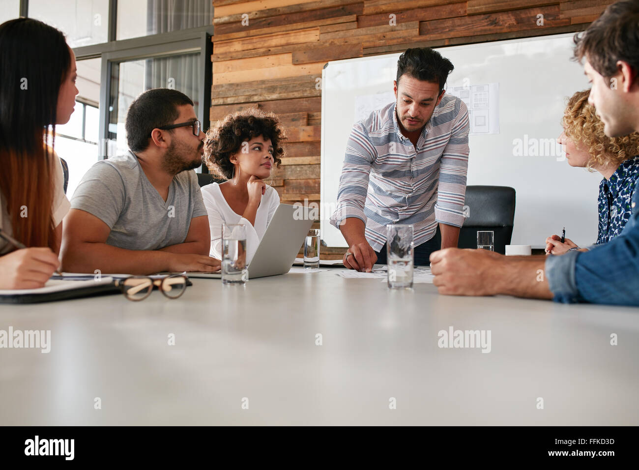 Young business team in a meeting discussing progress of the company. Creative professionals sitting around a table - Stock Image