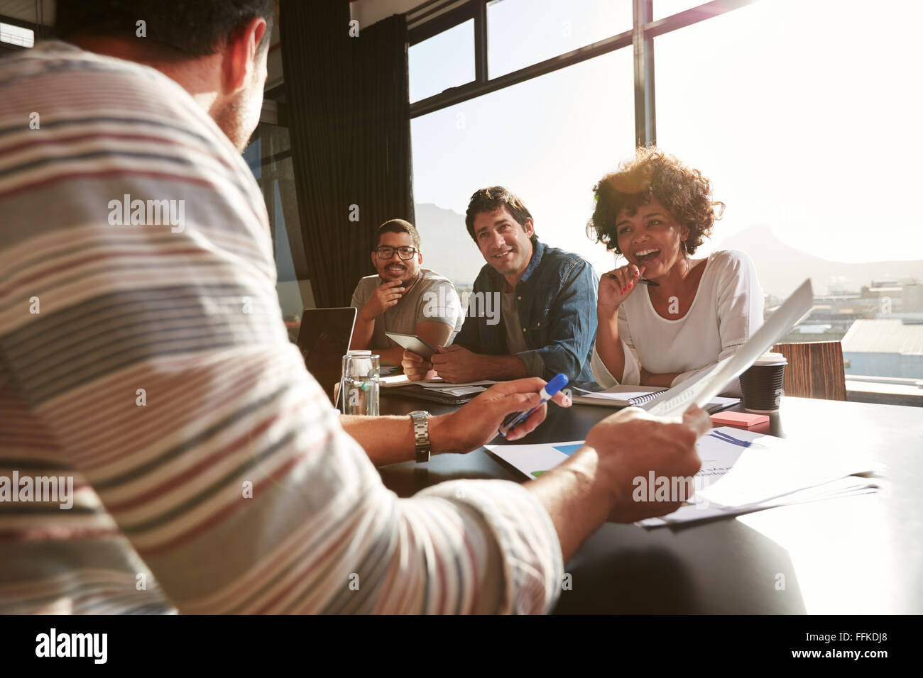Shot of mixed race young people sitting at a table discussing new and creative business ideas. Smiling african woman - Stock Image