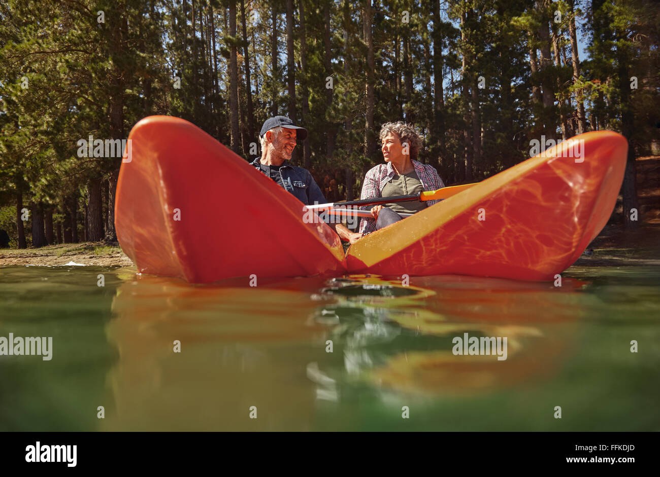 Active senior couple in two single kayaks side by side. Mature man and woman looking at each other and smiling while - Stock Image
