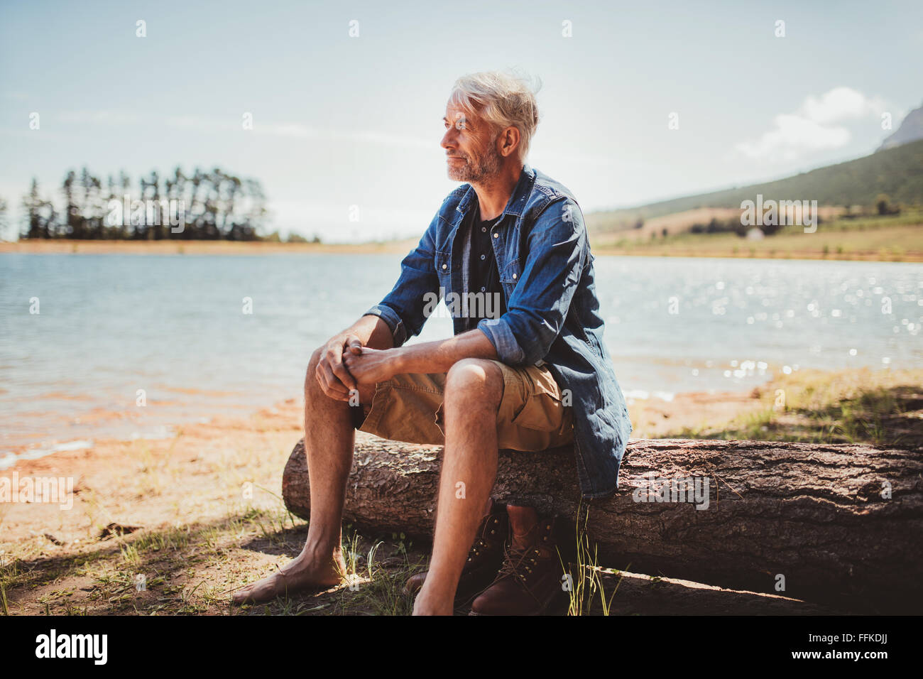 Portrait of a mature man sitting on a log near the lake. Senior caucasian man sitting alone on the lake and looking - Stock Image
