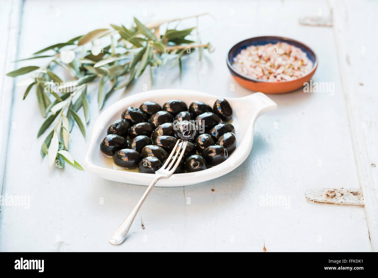 Black olives in white ceramic plate, branches and spices over light blue background, selective focus - Stock Image